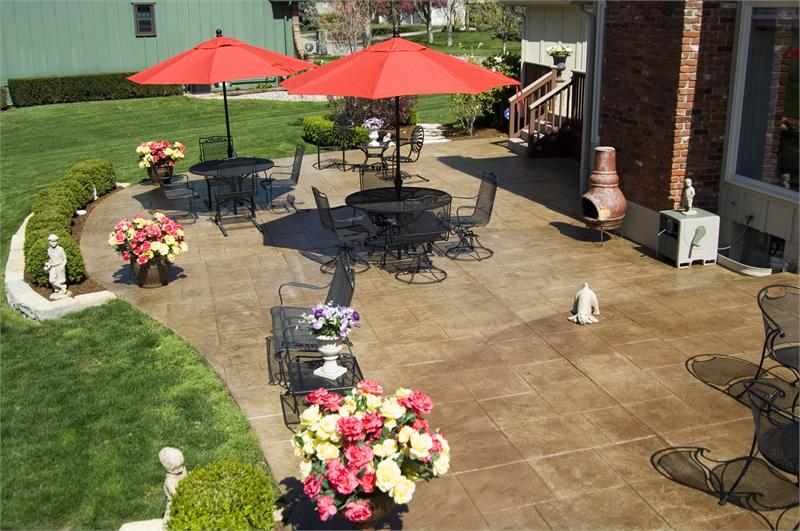 backyard stamped concrete patio ideas with wrought iron patio furniture and red umbrella top stamped concrete patio kansas city